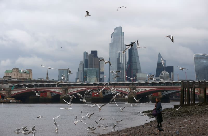 A woman feeds birds on the bank of the river Thames with London's financial district seen in the background, amid the coronavirus disease (COVID-19) in London