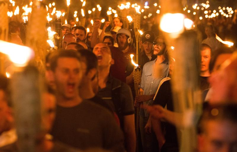 "White supremacists march through the University of Virginia campus in Charlottesville on Aug. 11, 2017, the night before holding a violent ""Unite The Right"" rally. (NurPhoto via Getty Images)"