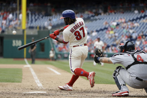 Philadelphia Phillies' Odubel Herrera, left, hits a home run off St. Louis Cardinals relief pitcher Sam Tuivailala during the seventh inning of a baseball game, Wednesday, June 20, 2018, in Philadelphia. At right is catcher Yadier Molina. Philadelphia won 4-3. (AP Photo/Matt Slocum)