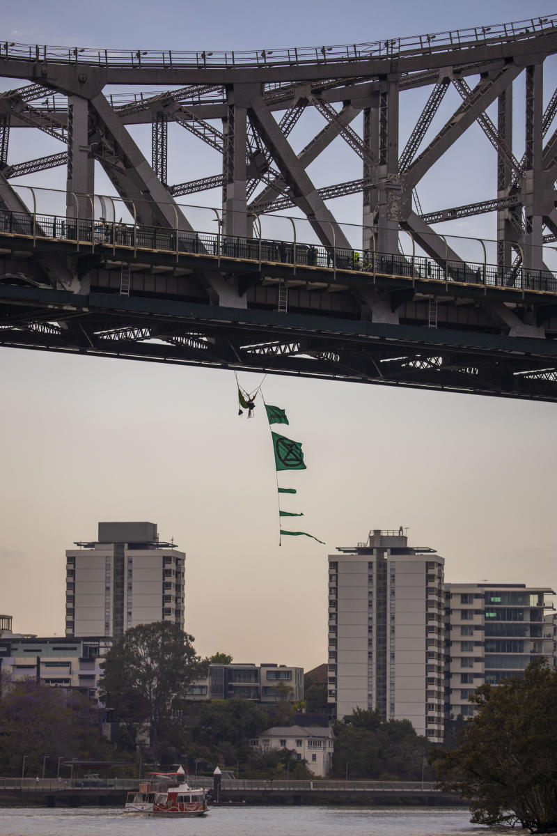 The activist hangs from the bridge with a series of flags. Source: AAP