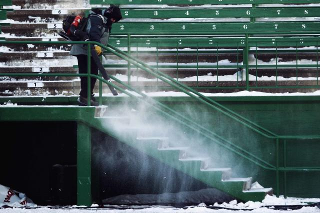A man uses a snow blower at the stands during the Saskatchewan Roughriders' team practice in Regina, Saskatchewan, November 22, 2013. The Saskatchewan Roughriders will play against the Hamilton Tiger-Cats in the CFL's 101st Grey Cup in Regina. REUTERS/Mark Blinch (CANADA - Tags: SPORT FOOTBALL)