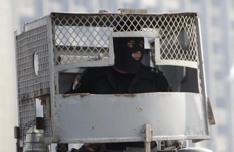 A riot policeman sits inside a police vehicle on October bridge during clashes with anti-government protesters and members of the Muslim Brotherhood, near Tahrir Square in downtown Cairo