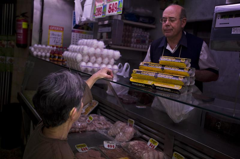 A woman pays in a market in Madrid in Madrid, Spain, Wednesday, April 17, 2013. European Central Bank President Mario Draghi urged the 17 European Union countries that use the euro on Tuesday to move swiftly toward completing a full banking union to stabilize the bloc's financial sector. (AP Photo/Daniel Ochoa de Olza)