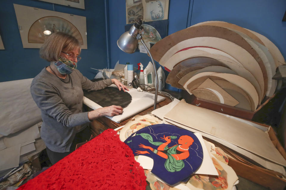 Anne Hoguet, 74, fan-maker and director of the hand fan-making museum works in her workshop in Paris, Wednesday, Jan. 20, 2021. Just like the leaves of its gilded fans, France's storied hand fan-making museum could fold up and vanish. The splendid Musee de l'Eventail in Paris, a classed historical monument, is the culture world's latest coronavirus victim. (AP Photo/Michel Euler)