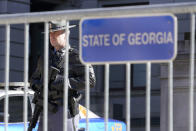 A Georgia State Patrol trooper stands guard outside the Georgia Capitol Friday, Jan. 15, 2021, in Atlanta. With the FBI warning of potential violence at all state capitols Sunday, Jan. 17, the ornate halls of government and symbols of democracy looked more like heavily guarded U.S. embassies in war-torn countries. (AP Photo/John Bazemore)