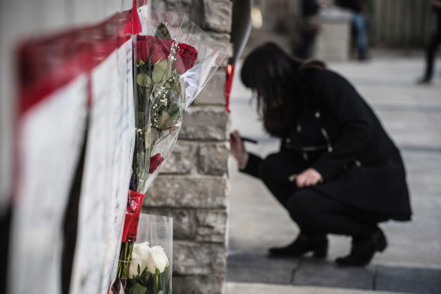 <p>Bouquets of flowers are placed at a makeshift memorial to the victims as a woman writes her condolences after a van mounted a sidewalk crashing into pedestrians in Toronto on Monday, April 23, 2018. (Photo: Aaron Vincent Elkaim/The Canadian Press via AP) </p>