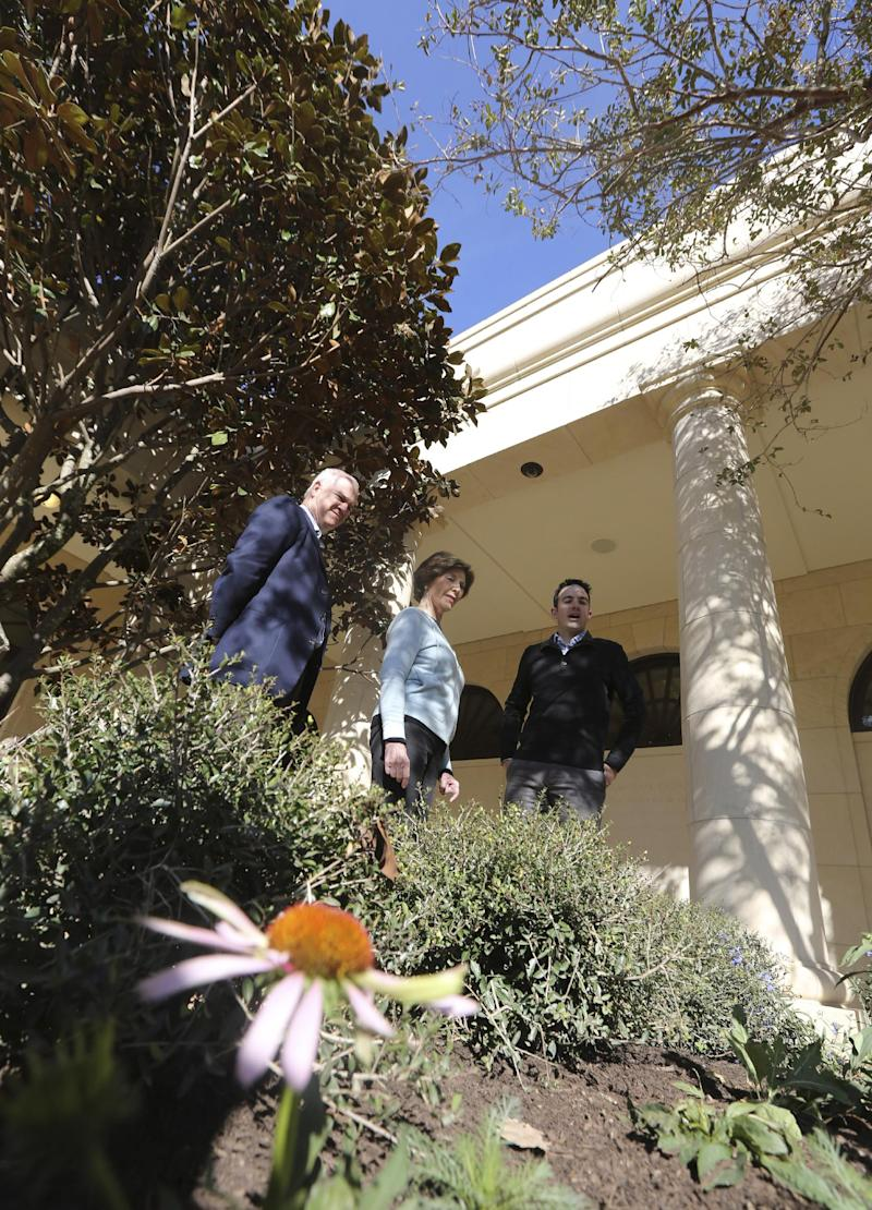 In this Monday, Oct. 29, 2012 photo, former first lady Laura Bush, center, talks with Herb Sweeney, right, landscape architect, and Mark Langdale, president of the George W. Bush Foundation, during a tour of the Texas interpretation of the White House Rose Garden at the George W. Bush Presidential Center in Dallas. A 15-acre park at the upcoming George W. Bush Presidential Center will recreate a Texas prairie, complete with a wildflower meadow, a special blend of native grasses and even trees transplanted from the former president's ranch.  (AP Photo/LM Otero)