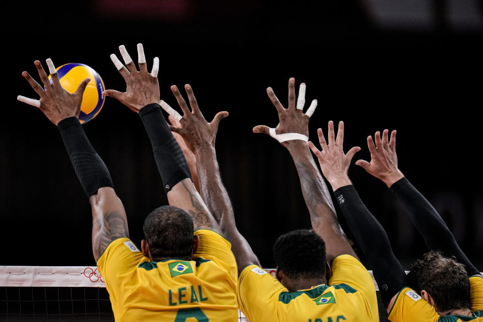 Brazil's team players block a ball during a men's volleyball preliminary round pool B match between Brazil and United States at the 2020 Summer Olympics, Friday, July 30, 2021, in Tokyo, Japan. (AP Photo/Manu Fernandez)