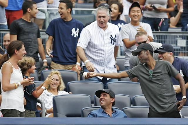 Comedian Chris Rock, far right, offers a foul ball he caught off Houston Astros' Marwin Gonzalez to a youngster after catching it in the seventh inning of a baseball game against the New York Yankees at Yankee Stadium in New York, Thursday, Aug. 21, 2014. (AP Photo/Kathy Willens)