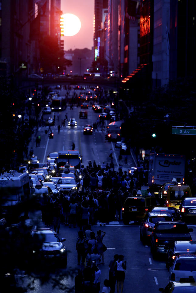 People stand in the middle of 42nd Street in New York's Manhattan borough as the sun sets through the middle of the buildings during a phenomenon known as Manhattanhenge, Wednesday, July 11, 2012. Manhattanhenge, sometimes referred to as the Manhattan Solstice, happens when the setting sun aligns with the east-to-west streets of the main street grid. The term references Stonehenge, at which the sun aligns with the stones on the solstices in England. (AP Photo/Julio Cortez)