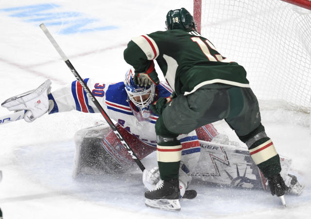 Minnesota Wild's Luke Kunin, right, loses his stick as he attempts to get off a shot against New York Rangers goalie Henrik Lundqvist, left, of Sweden, in the second period of an NHL hockey game Saturday, March 16, 2019, in St. Paul, Minn. The Wild beat the Rangers 5-2. (AP Photo/Tom Olmscheid)