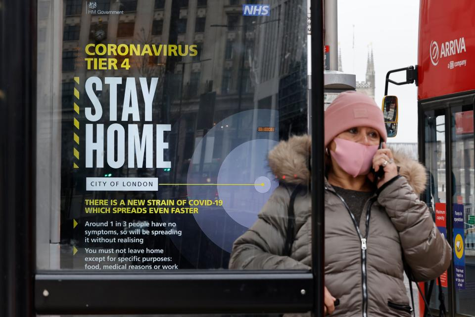"A passenger wearing a mask because of the coronavirus pandemic talks on the telephone waiting at a bus stop with a government message about the coronavirus tier 4 restrictions urging people to stay home in London on December 29, 2020. - England is ""back in the eye"" of the coronavirus storm, health chiefs warned Tuesday, with as many patients in hospital as during the initial peak in April. (Photo by Tolga Akmen / AFP) (Photo by TOLGA AKMEN/AFP via Getty Images)"