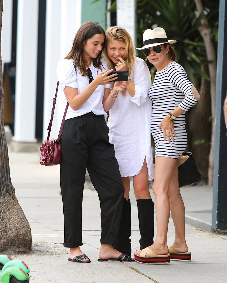 <p>Ana de Armas smiles while showing friends something on her phone on Tuesday in L.A. </p>