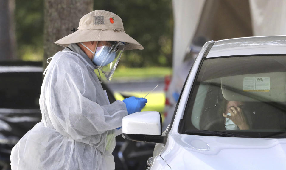 A medical professional prepares to apply a nasal swab during testing at the Orange County Health Services COVID-19 drive-thru site at Barnett Park in Orlando, Fla., Thursday, Oct. 29, 2020. The free tests are available 8am to 1pm daily at the park adjacent to the Central Florida Fairgrounds on West Colonial Drive. (Joe Burbank /Orlando Sentinel via AP)