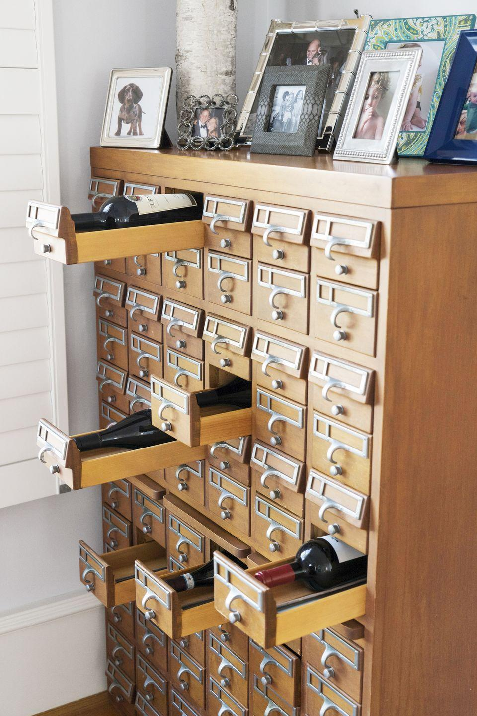 <p>A bottle of wine fits perfectly into a drawer of an old card catalog. Drawers without wine offer a perfect spot to stash birthday and other holiday cards.</p>