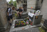 Joachim Tittmar from Germany, left, Walter Homburg of Netherland, center, and his girlfriend Kate Schirm gather at the tomb of rock singer Jim Morrison at the Pere-Lachaise cemetery in Paris, Saturday, July 3, 2021. Fans across Europe gathered at the grave of rock legend Jim Morrison to mark the 50th anniversary of his death. (AP Photo/Michel Euler)