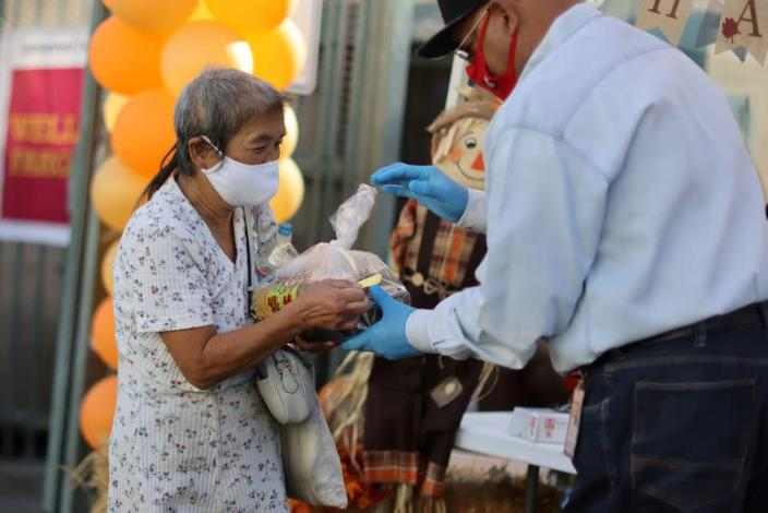 FILE PHOTO: A woman picks up food at a Los Angeles Mission homeless shelter Thanksgiving meal giveaway in Los Angeles
