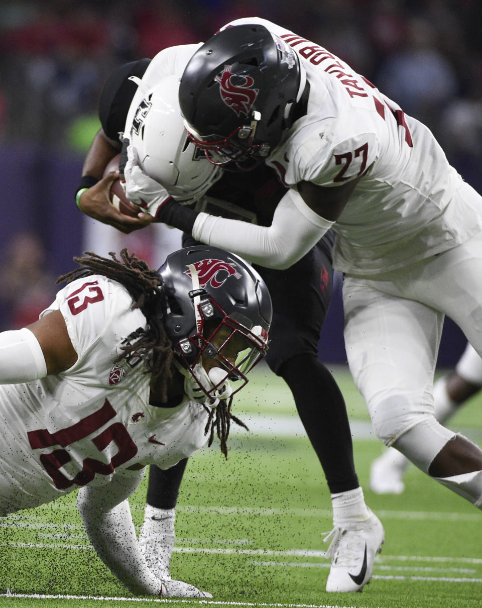 Houston quarterback D'Eriq King, center, escapes the sack attempt of Washington State's Willie Taylor III (27) and linebacker Jahad Woods (13) during the first half of an NCAA college football game Friday, Sept. 13, 2019, in Houston. (AP Photo/Eric Christian Smith)