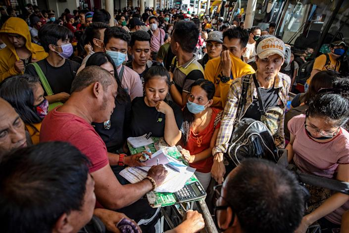 Filipinos hoping to leave Manila before it is placed on lockdown flock at a bus station on March 13, 2020 in Quezon city, Metro Manila, Philippines.