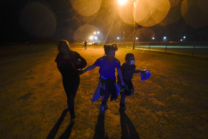 FILE - In this May 11, 2021, file photo, three young migrants hold hands as they run in the rain at an intake area after turning themselves in upon crossing the U.S.-Mexico border in Roma, Texas. The Biden administration says the number of unaccompanied migrant children housed at its largest emergency shelter has dropped by more than 40% since mid-June. (AP Photo/Gregory Bull, File)