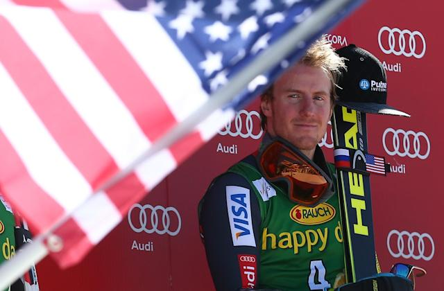 Ted Ligety of the United States listens to the national anthem after winning an alpine ski men's World Cup giant slalom, in Kranjska Gora, Slovenia, Saturday, March 8, 2014. (AP Photo/Giovanni Auletta)