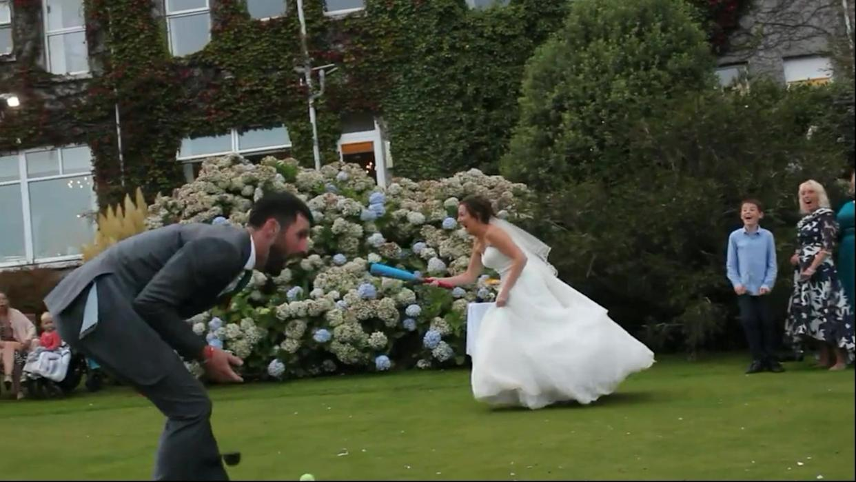 Video grab of the unfortunate moment a bride playing a game of rounders at her wedding smacked a ball - into her new husband's groin.