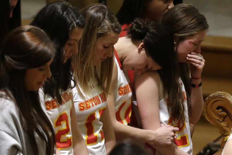 Members of the Seton Hill University's women's lacrosse team attend a memorial mass in St. Joseph Chapel on  the school's  Greensburg, Pa., campus Sunday, March 17, 2013. Women's lacrosse coach Kristina Quigley and the tour bus driver were killed when their tour bus carrying three coaches and members of the lacrosse team when the bus crashed at about 9 a.m., turnpike spokeswoman Renee Colborn said. It's not clear what caused the crash, but state police were investigating, said Megan Silverstram of the Cumberland County public safety department. (AP Photo/Gene J. Puskar)