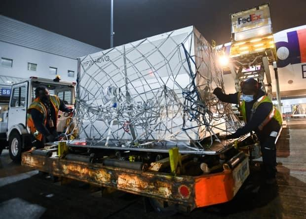 FedEx workers offload a plane carrying 255,600 doses of the Moderna COVID‑19 vaccine which came from Europe during the COVID-19 pandemic at Pearson International Airport in Toronto on Wednesday, March 24.