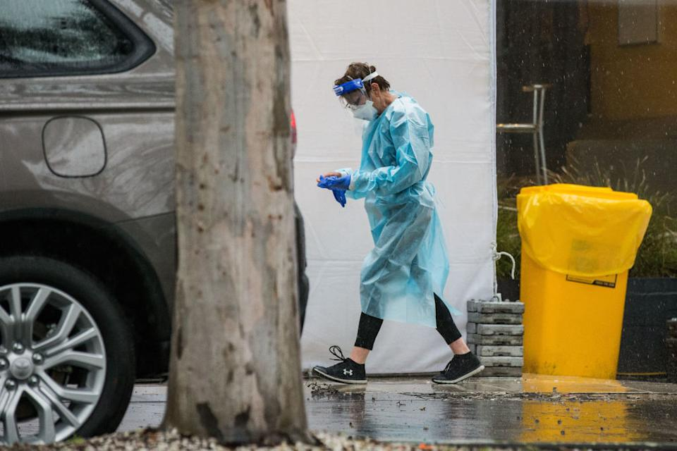 A woman wearing PPE (Personal Protective Equipment) is seen outside the Quality Hotel Carlton.