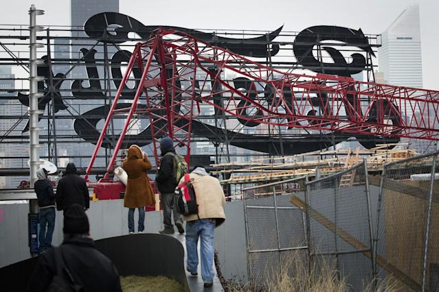 """Onlookers observe a mangled crane at the construction site in the Queens borough of New York where it collapsed, Wednesday, Jan. 9, 2013 behind a big neon """"Pepsi Cola"""" sign, a local landmark. The Fire Department of New York says the 200-foot crane collapsed onto a building under construction, injuring seven people, three of them seriously. (AP Photo/John Minchillo)"""