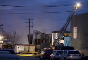 Emergency crews are shown outside Neptune Technologies in Sherbrooke, Que., Thursday, November 8, 2012 where a large explosion at the plant sent a number of people to hospital with serious injuries. THE CANADIAN PRESS/Graham Hughes.