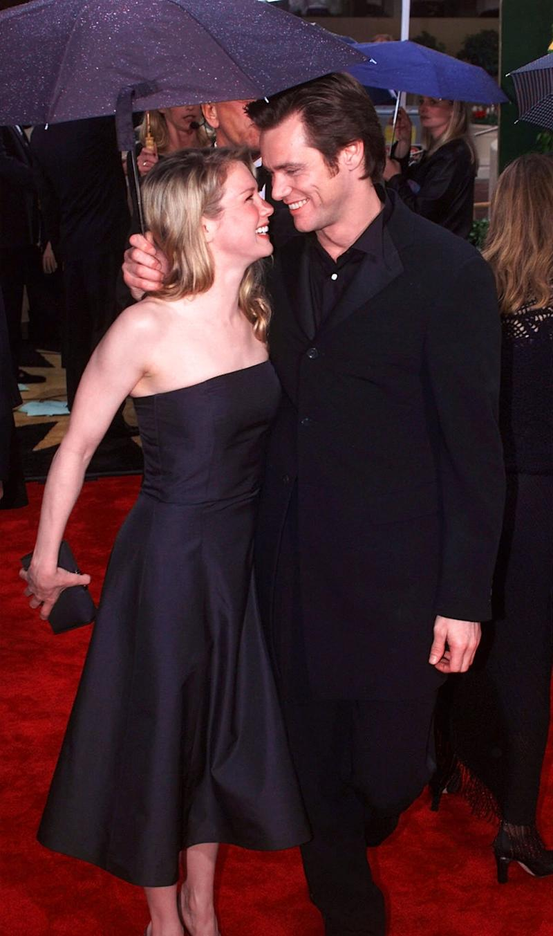 "Jim Carrey, right, nominated for best actor in a musical or comedy film for his role in ""Man on the Moon,"" arrives with Renee Zellweger at the 57th Golden Globe Awards in Beverly Hills, Calif., Sunday Jan. 23, 2000. (AP Photo/Mark J. Terrill)"