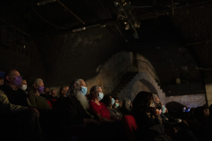 The audience wearing protective face masks watches on opening night at the Khan Theater during a performance where all guests were required to show proof of receiving a COVID-19 vaccination or full recovery from the virus, in Jerusalem, Tuesday, Feb. 23, 2021. (AP Photo/Maya Alleruzzo)