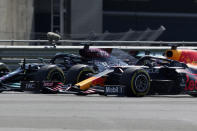 Mercedes driver Lewis Hamilton of Britain, left, and Red Bull driver Max Verstappen of the Netherlands take a curve side-by-side at the start of the British Formula One Grand Prix, at the Silverstone circuit, in Silverstone, England, Sunday, July 18, 2021. (AP Photo/Jon Super)