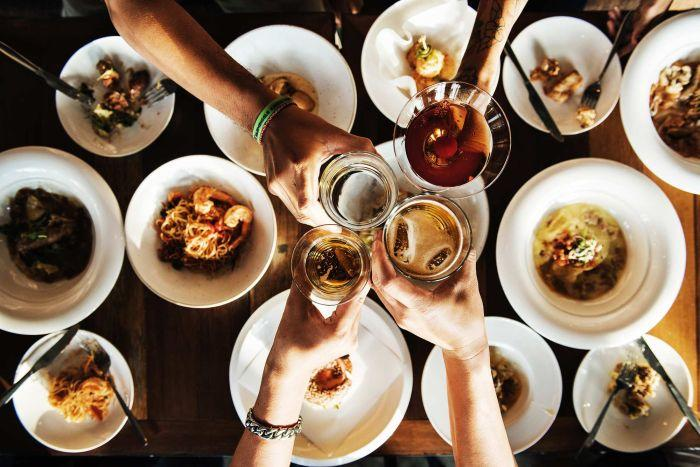 Top down shot of four toasting alcoholic drinks above a dinner table to illustrate dinner party.