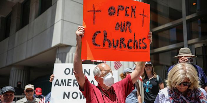 Demonstrators holding signs demanding their church to reopen, protest during a rally to re open California and against Stay At Home directives on May 1, 2020 in San Diego, California.