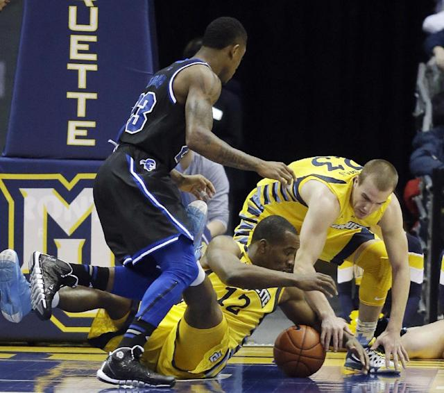 Marquette's Derrick Wilson (12) and Jake Thomas go after a loose ball with Seton Hall's Fuquan Edwin during the first half of an NCAA college basketball game Saturday, Jan. 11, 2014, in Milwaukee. (AP Photo/Morry Gash)