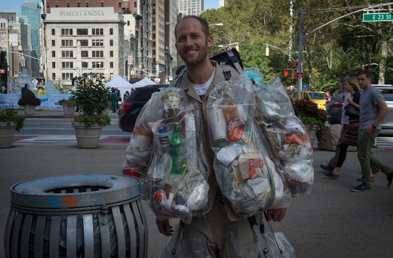 Rob Greenfield, an environmental activist who is spending a month in New York, has hanging on himself all the trash he's produced in ziplog bags on October 4, 2016 in New York (AFP Photo/Bryan R. Smith)
