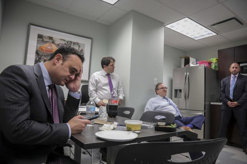 In this Tuesday, Oct. 29, 2019, photo, attorney Adam Slater, left, checks his phone during a working lunch with lawyers in his firm including partner Jonathan Schulman, second from left, Steven Alter, second from right, and Linc Leder, in Melville, N.Y. Slater said since New York state opened its one-year window allowing sex abuse suits with no statute of limitations, his firm has signed up nearly 300 new clients. (AP Photo/Bebeto Matthews)