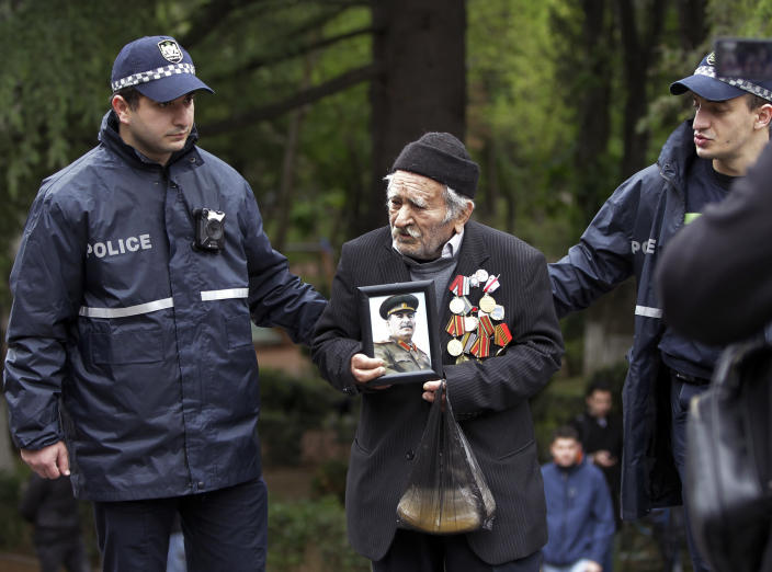 Police officers help Vakhtang Adamashvili, 94, veteran of the WWII with a portrait a portrait of Soviet dictator Josef Stalin to attend a laying ceremony at a war memorial in the Victory Park marking the 75th anniversary of the Nazi defeat in World War II in Tbilisi, Georgia, Saturday, May 9, 2020. (AP Photo/Shakh Aivazov)