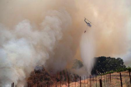 """A helicopter drops water on the fast-moving wildfire called """"Sand Fire,"""" near Plymouth, California July 26, 2014. REUTERS/Max Whittaker"""