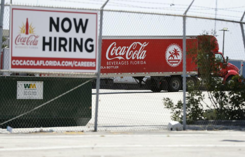 A tractor trailer truck backs into a loading dock at Coca-Cola Beverages Florida past a Now Hiring sign