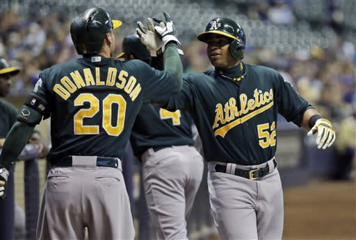 Oakland Athletics' Yoenis Cespedes (52) is congratulated by Josh Donaldson after Cespedes hit a two-run home run during the first inning of a baseball game against the Milwaukee Brewers on Tuesday, June 4, 2013, in Milwaukee. (AP Photo/Morry Gash)