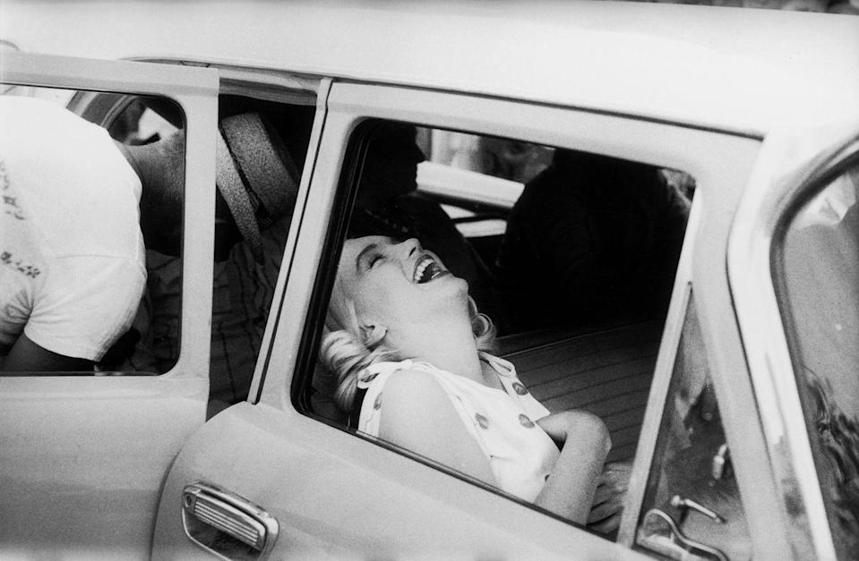 <p>Marilyn Monroe laughing in the front seat of a car during the filming of The Misfits on location in the Nevada Desert.</p>