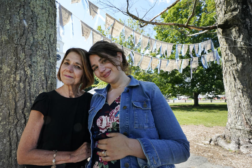 """Widow Marcy Jacobs, left, stands with her daughter, Jaclyn Winer, under flags bearing names of people, including her husband, Keith Jacobs, who have died from COVID-19, outside the First Congressional Church, Thursday, June 17, 2021, in Holliston, Mass. The flags are part of the COVID Art and Remembrance project spearheaded by Jaclyn. """"Don't expect us to move on without giving us a place to grieve,"""" Marcy Jacobs said, recalling her husband as kind, uncomplaining and simple. """"Is it a stone for everyone? I don't know."""" (AP Photo/Elise Amendola)"""