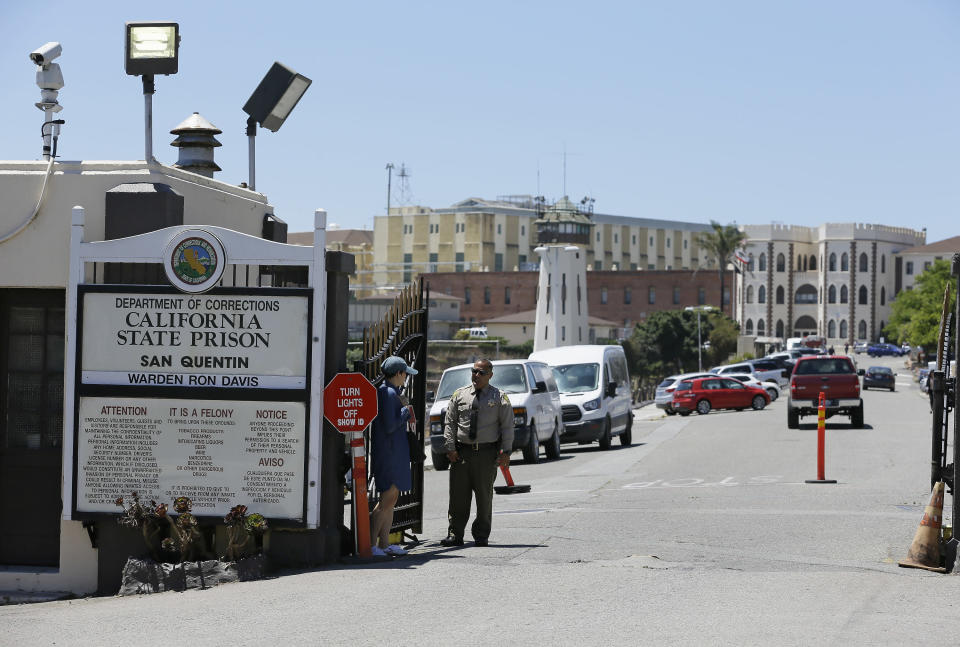 """FILE - A Department of Corrections officer guards the main entryway leading into San Quentin State Prison in San Quentin, Calif., July 24, 2019. California lawmakers harshly criticized state corrections officials Wednesday, July 1, 2020, for a """"failure of leadership"""" for botching their handling of the pandemic by inadvertently transferring infected inmates to an untouched prison, triggering the state's worst prison coronavirus outbreak. A third of the 3,500 inmates at San Quentin State Prison near San Francisco have tested positive since officials transferred 121 inmates from the heavily impacted California Institution for Men in Chino on May 30 without properly testing them for infections. (AP Photo/Eric Risberg, File)"""