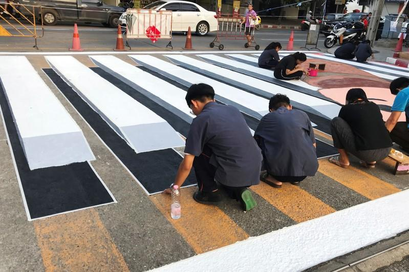 People paint a 3D pedestrian crossing in Bangkok