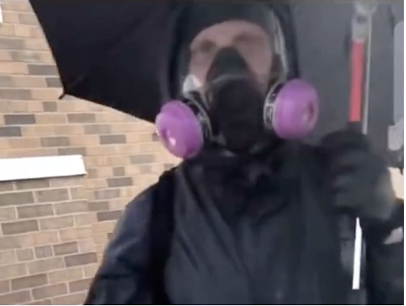 A man dressed in a gas mask and holding an umbrella who was filmed calmly smashing windows. Some have suggested he may have been an agent provocateur