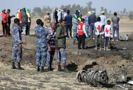 Ethiopian Federal policemen stand near engine parts at the scene of the Ethiopian Airlines Flight ET 302 plane crash, near the town of Bishoftu