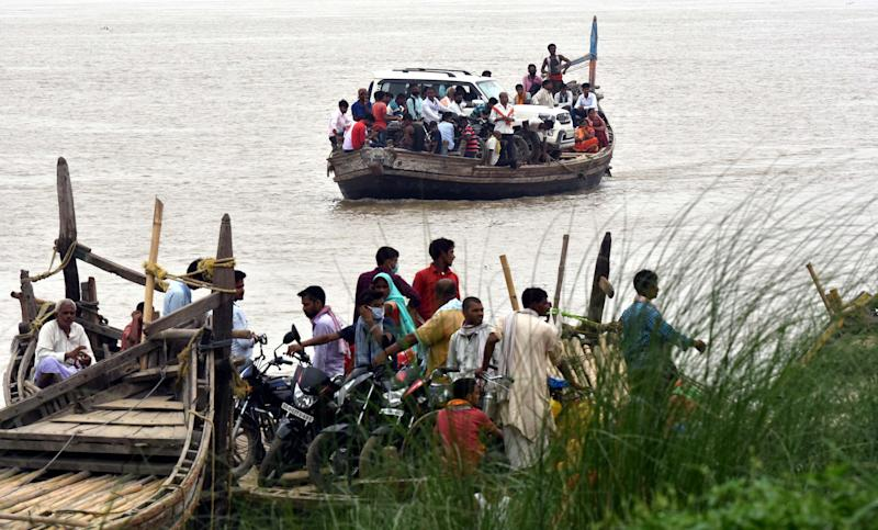 Residents of the lower lying area between the Patna district and Vaishali District taking life risk with their belongings crossing the Ganga River by overcrowded boat the water level of the rises, leading to a flood-like situation and ignoring the social distancing ongoing pandemic Covid-19 in Kacchi Dargah area on July 2, 2020 in Patna, India. (Photo by Parwaz Khan/Hindustan Times via Getty Images)